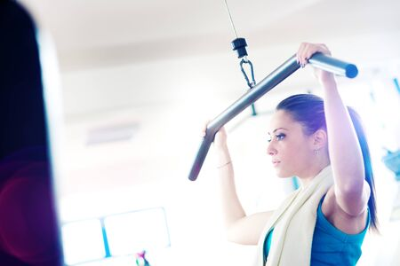 Beautiful young girl at gym working out on exercising machine.