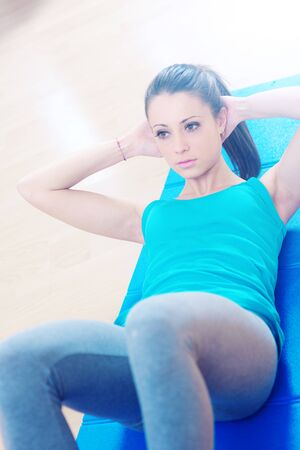 Attractive woman doing abs workout at gym for muscle toning and flat stomach. Фото со стока