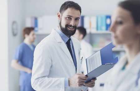 Confident doctor checking medical records on a clipboard and smiling at camera Stockfoto - 146851450