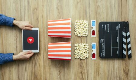 Man watching movies streaming online using a digital tablet, popcorn, 3D glasses and clapboard, cinema and entertainment concept Banco de Imagens
