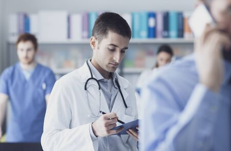 Confident doctor checking medical records on a clipboard, he is holding a pen, medical staff on the background, healthcare and medical services concept Stockfoto - 146851451