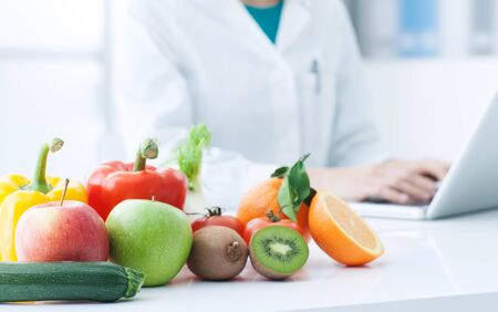 Colorful tasty fruits and vegetables on the dietician's desk, the doctor is typing on a laptop in the background, healthy diet concept