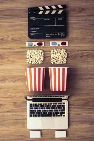 Laptop, clapper board, popcorn and 3D glasses: cinema streaming and movie series online concept Banco de Imagens