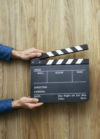 Film director holding a clapper board, filmmaking and cinema concept