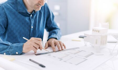 Professional architect working at office desk, he is drawing and making measurements on a project blueprint, design and architecture concept