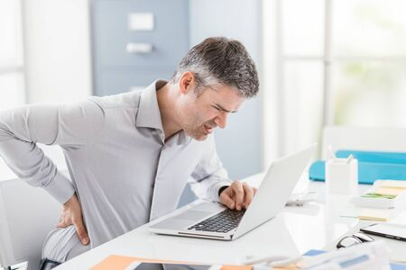 Stressed businessman with backache, he is working at office desk and massaging his back