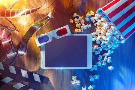 Digital touch screen tablet with popcorn, 3D glasses and filmstrip; movie online streaming cinema and entertainment concept