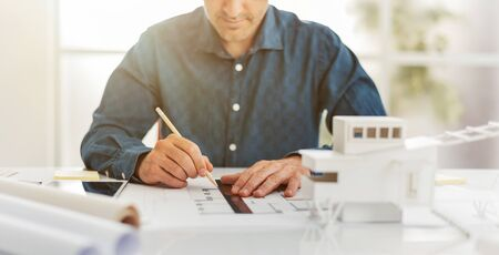 Professional architect working at office desk, he is drawing with a ruler on a draft project, architecture and engineering concept