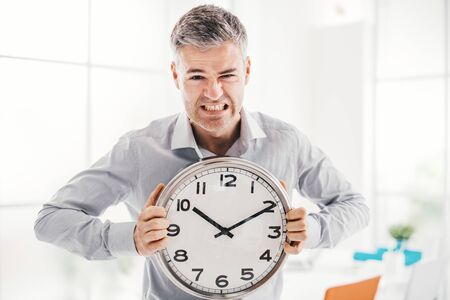 Business, time management and deadlines: angry businessman holding a clock, he is late and missing a deadline Stok Fotoğraf