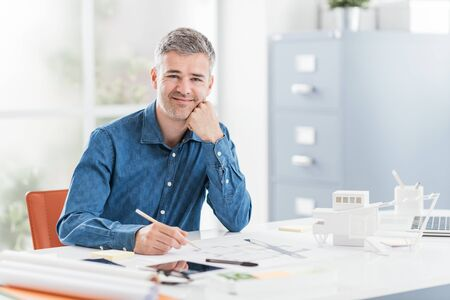 Professional architect sitting at office desk and working, he is checking a project blueprint, engineering and architecture concept Archivio Fotografico
