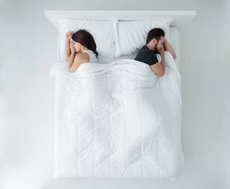 Young couple sleeping in bed back to back, top view