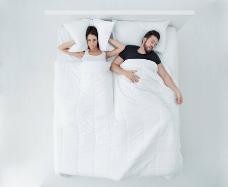 Sleepless woman in bed, she is covering her ears with a pillow, her boyfriend is snoring, top view