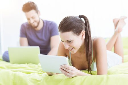 Young couple relaxing in bed, they are connecting to the internet using a laptop and a digital tablet 写真素材