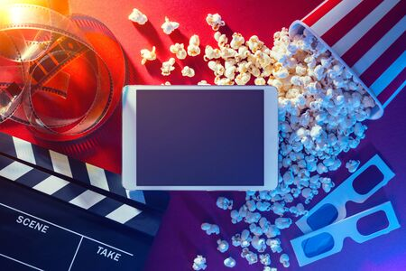 Blank digital tablet, popcorn, 3D glasses and filmstrip, cinema and movie online streaming concept Banco de Imagens