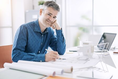 Confident professional architect posing in his office and smiling at camera, he is sitting at desk and working on a building project blueprint Archivio Fotografico