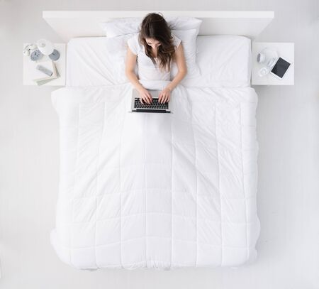 Young happy woman relaxing in her bed, she is connecting with a laptop, top view