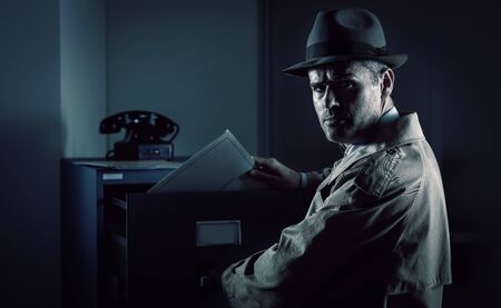 Vintage undercover spy stealing files in a filing cabinet late at night, security, data theft and crime concept