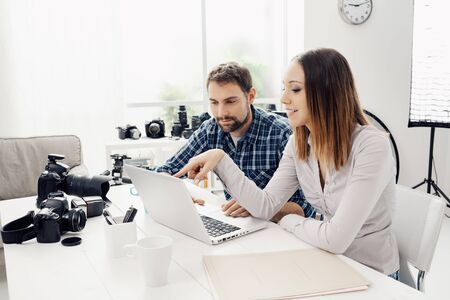 Photographer and designer in a creative agency, they are sitting at desk and working together with a laptop Stock Photo