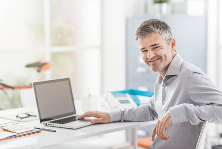 Confident office worker sitting at office desk and working with a laptop, he is smiling at camera Stock Photo