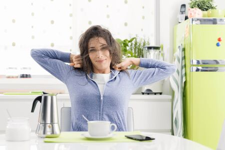Tired lazy woman having breakfast at home in the kitchen, she is stretching and having a coffee Stock Photo