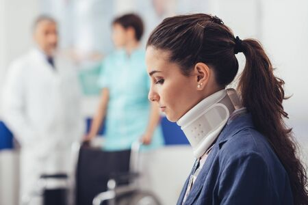 Young female patient with cervical collar support at the hospital, she is sitting in the waiting room, medical staff on the background Imagens