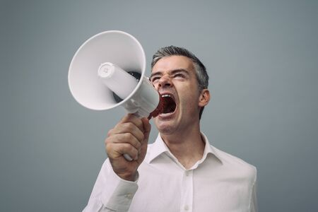 Aggressive man shouting with a megaphone and spreading his message, advertising and communication concept