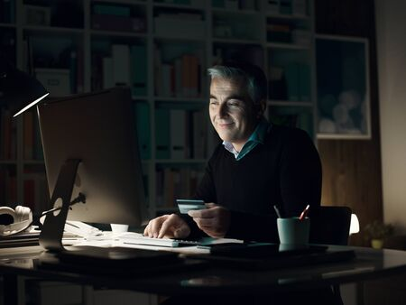 Smiling cheerful man connecting late at night with his computer and doing online shopping using a credit card
