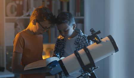 Smart kids using a telescope and studying astronomy together, they are searching informations in a book