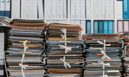 Stacks of files and paperwork in the office and bookshelves on the background: management and storage concept