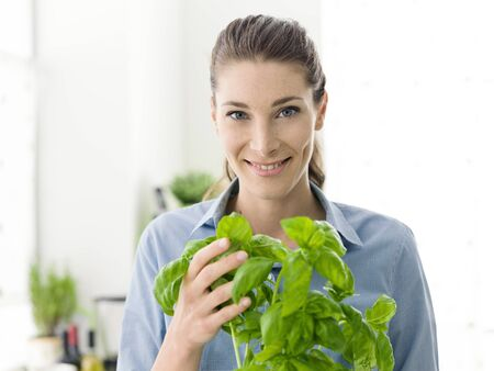 Young woman growing fresh herbs at home, she is holding a plant of basil and smiling at camera