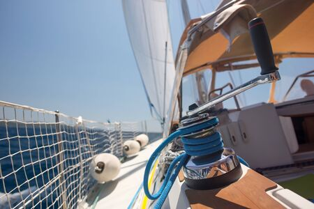 Winch with rope on a sail boat close up: travel, sailing and adventure concept