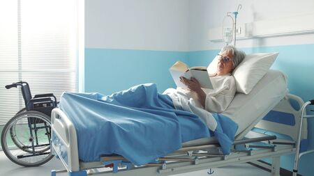 Senior woman lying in bed at the hospital and reading a book Banque d'images