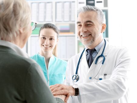 Professional smiling doctor helping and supporting a senior patient, he is holding her hand, healthcare and geriatrics concept