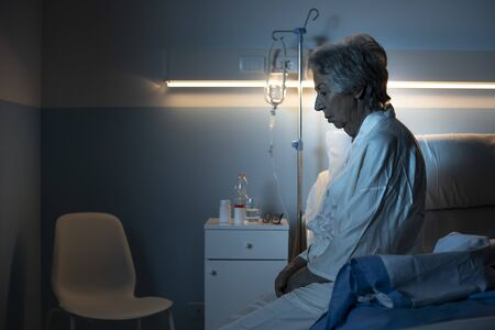 Lonely senior patient suffering from insomnia and sitting on the hospital bed at night