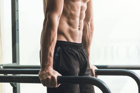 Muscular shirtless young man exercising at the gym on dip bars, fitness and sports concept
