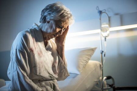 Lonely senior patient suffering with headache, she is sitting on the hospital bed and feeling sad
