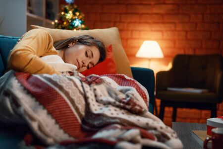Young woman sleeping on the sofa under a warm blanket, Christmas tree in the background