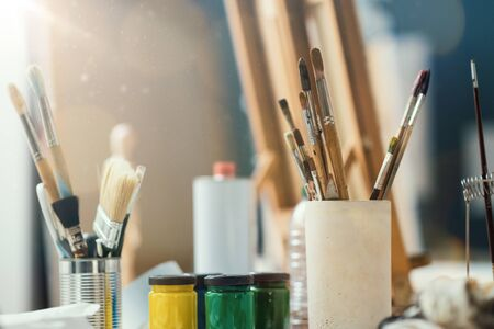 Assorted fine arts supplies for painting on a desk in the art studio, oil and acrylic paint