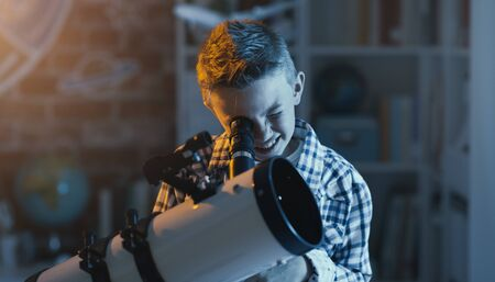 Cute boy watching stars through a telescope at night in his bedroom Stockfoto - 147597167