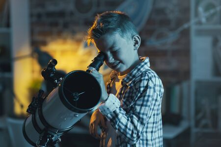 Cute boy watching stars through a telescope at night in his bedroom