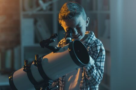Cute boy watching stars through a telescope at night in his bedroom Stockfoto - 147597168