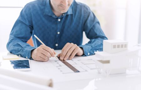 Professional architect working at office desk, he is drawing with a ruler on a draft project, architecture and design concept