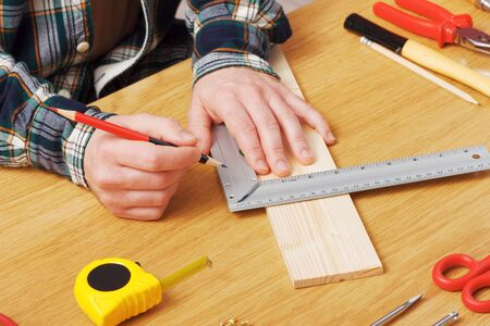 Man working on a DIY project and measuring a wooden plank with work tools all around, hands close up Imagens