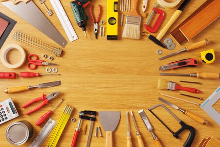 DIY and home improvement banner with work and construction tools on a wooden workbench top view, copy space at center Foto de archivo