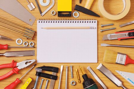 Home DIY and improvement concept, blank notebook with work tools all around on a wooden table, top view