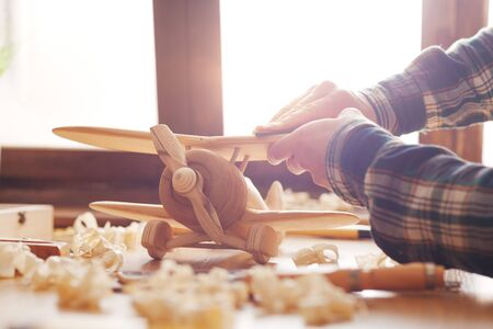 Craftsman smoothing a wooden toy surface with sandpaper, tools and wood shavings all around, hands close up
