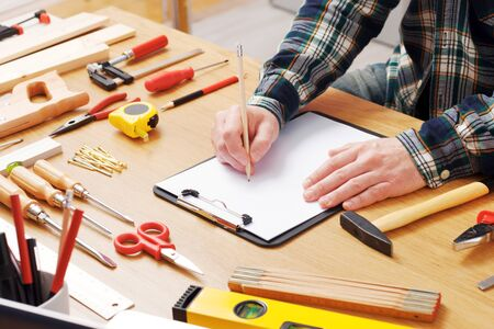 Man sketching a DIY project on a clipboard with work tools all around, hands close up, hobby and craft concept