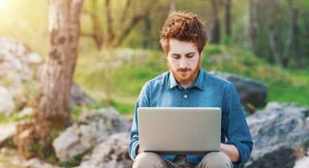 Young hipster man working on his laptop outdoors in nature, trees and plants on background