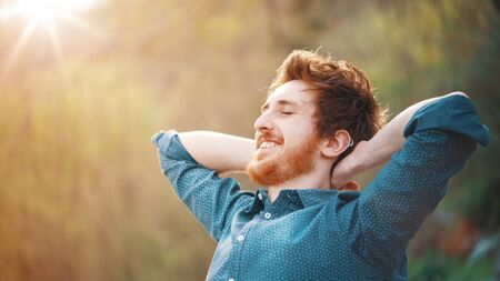 Happy young hipster man relaxing outdoors with hands behind head, nature and vegetation on background