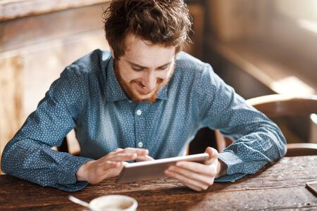 Cheerful hipster enjoying and social networking with his tablet during a coffee break Stockfoto